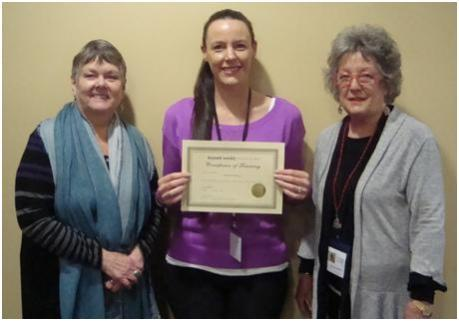 Laura receiving her graduation certificate after volunteer training, with Beyond Words team members, Carol and Wendy.